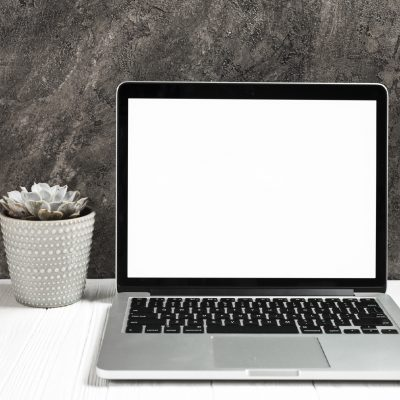 open-laptop-with-blank-white-screen-wooden-desk-against-black-wall-01